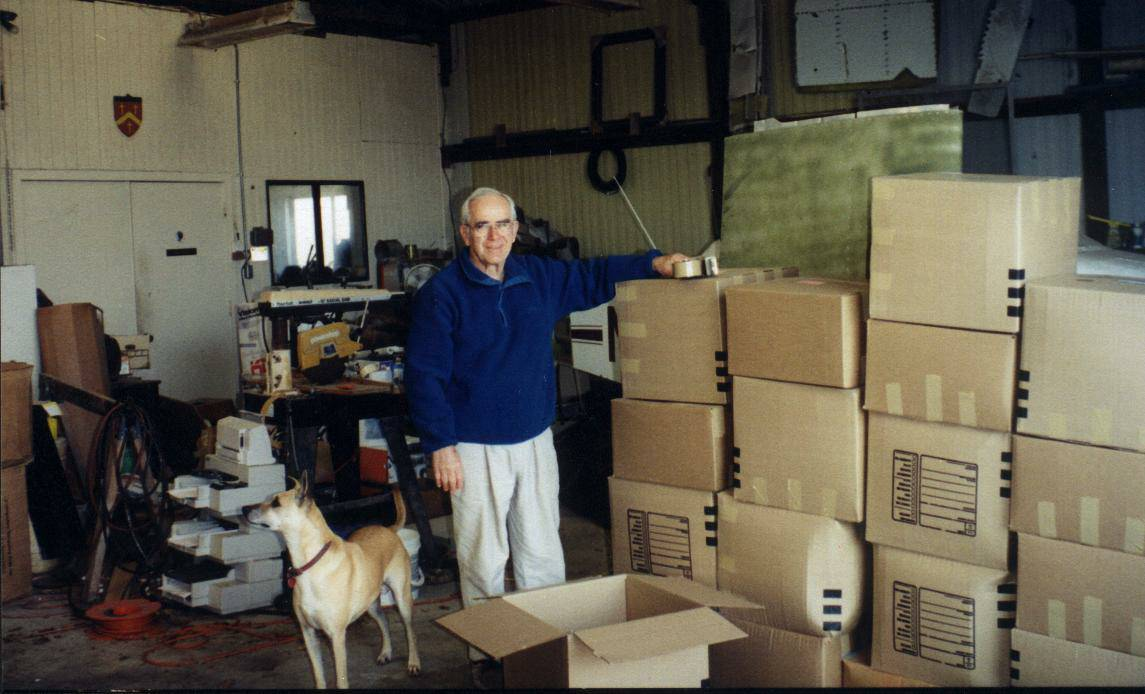 Getting boxes ready to ship out from his airplane hangar. It took more boxes to ship the computers back then.